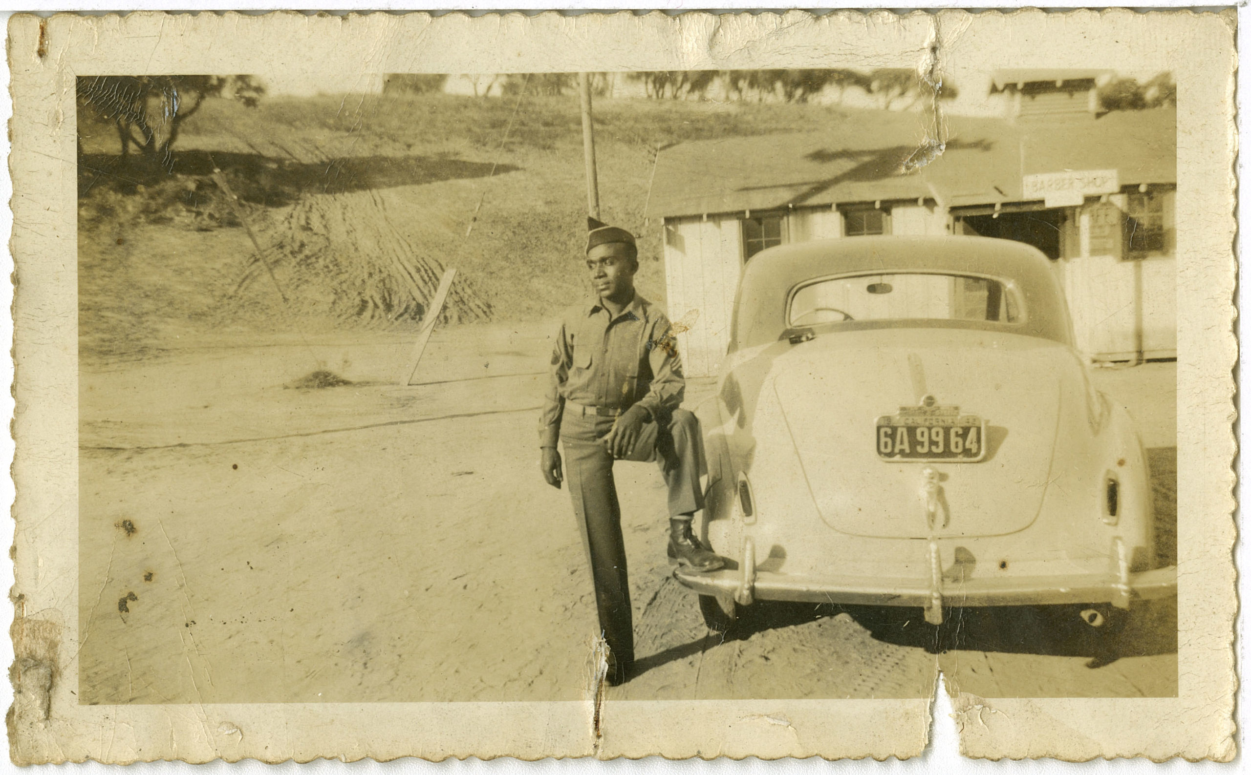 Photograph of soldier against a car, undatedAsh Family Photographs