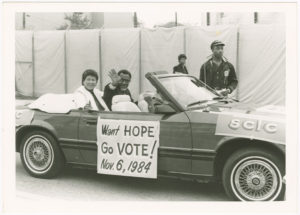Dr. Joseph Echols Lowery and Evelyn Gibson Lowery waving while riding in car with sign
